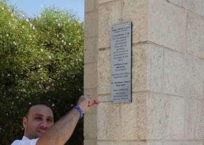 Pastor Saleem attaching plaque